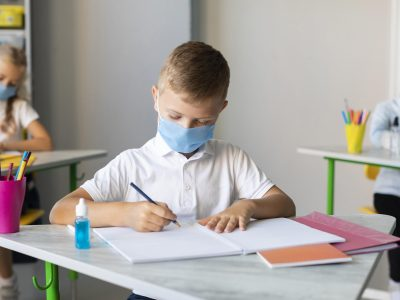 kids-writing-in-classroom-while-wearing-medical-masks