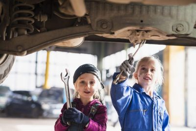 two-little-girls-in-overalls-repairing-car-with-spanners